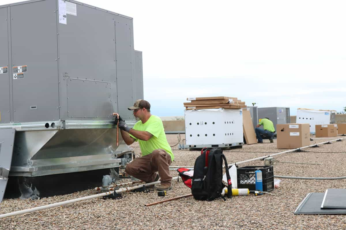 HVAC Techs installing commercial air conditioners