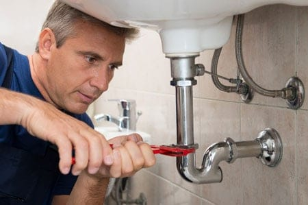 Plumber fixing leaking faucet in Garland, TX